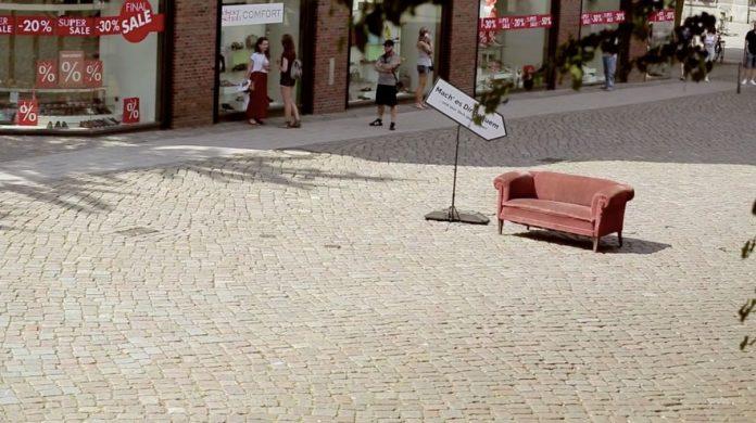 Divano posizionato al centro di una piazza ad Amburgo con un cartello che invita ad accomodarsi